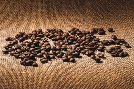 Coarse coffee beans, roasted and not ground, are scattered on a textured fabric with a burlap in warm colors. Stock fotó