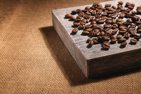 Large coffee beans, roasted and not ground, are scattered on a gray textured wooden board, which lies on a table covered with a coarse burlap cloth. Stock fotó