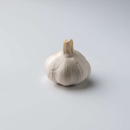 A large head of garlic, peeled in places, lies in the center against a white-gray background and casts a small soft shadow.