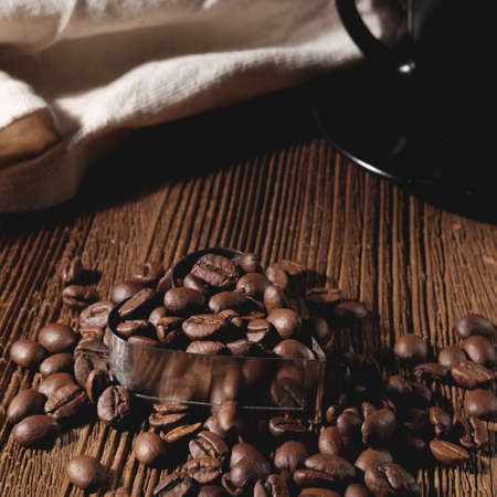 The coffee beans lie on a wooden table in a heart-shaped metal, in a low dark key and in a square proportion.