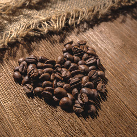 A large heart is laid out of coffee beans on a textured wooden table, in square proportions and a low key. Stock fotó