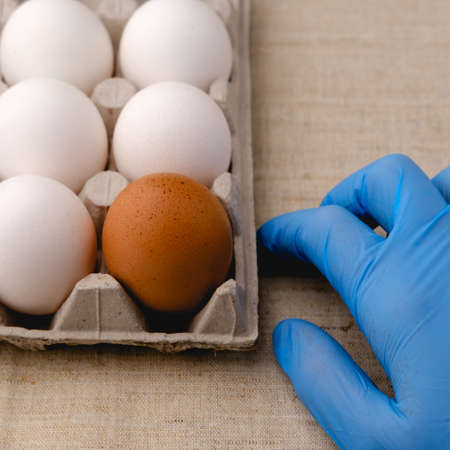 On a table with a light-colored ragcloth is a paper tray with white and brown eggs, and next to it is a hand wearing a disposable blue glove.