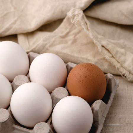 White and brown eggs lie side by side in a paper tray on the table, against a background of textured fabric with visible dents.