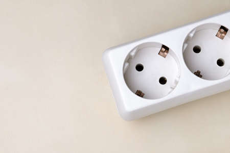 A white portable electrical outlet-splitter for several plugs lies on the right diagonally on a light surface, top view.