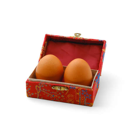 Two dark chicken eggs lie in a patterned reddish box, made in Chinese style, on a pure white isolated background with shadows, in a square orientation.