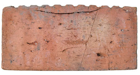 A light red brick, with lots of chips, cracks and depressions, with a top ribbed side on a clean white isolated background. Stock fotó