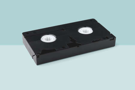VHS videotape in black with magnetic tape lies isolated on  light turquoise Stock fotó