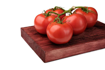 Red tomatoes on a green branch lie on a painted wooden board and are isolated on a clean white background.
