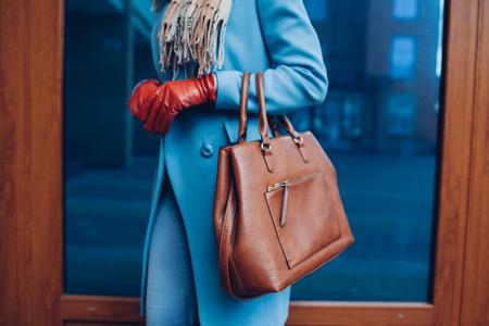 Schönheit und Mode. Stilvolle modische Frau mit Mantel und Handschuhen, die eine braune Handtasche hält.