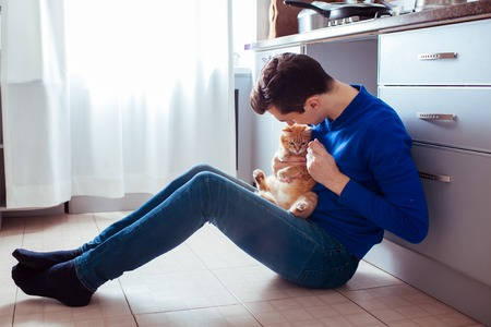 young man sitting on the floor of the kitchen with a cat.