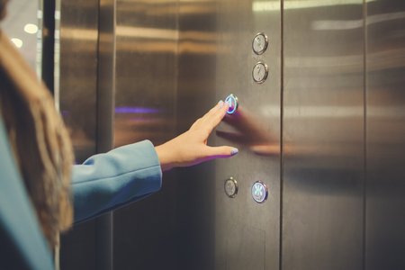 Woman Standing In Elevator And Pressing Button. Imagens