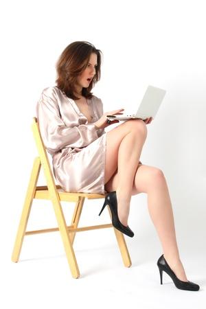 La jeune et belle fille en robe de chambre brillante avec étonnement regarde dans le portable