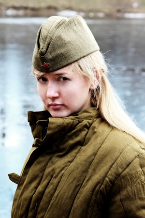 The girl the guerrilla of the period of the Second World War in the military form with the German automatic machine photo
