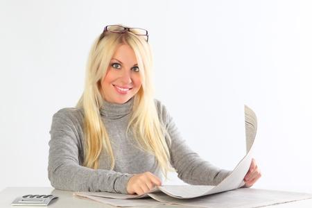 La mujer de negocios con gafas con los periódicos y el portátil funciona detrás de una mesa Foto de archivo - 9641127