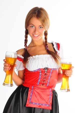 The girl in a traditional Bavarian dress with full glasses of beer in hands photo