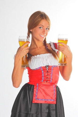The girl in a traditional Bavarian dress with full glasses of beer in hands Stock Photo - 10632285