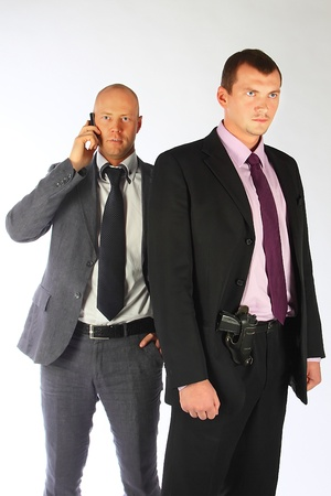 guarding: The businessman and the bodyguard with a pistol