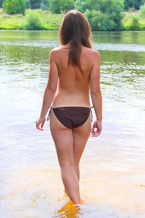 hot breast: The young and beautiful girl in a bathing suit has a rest on a wood beach
