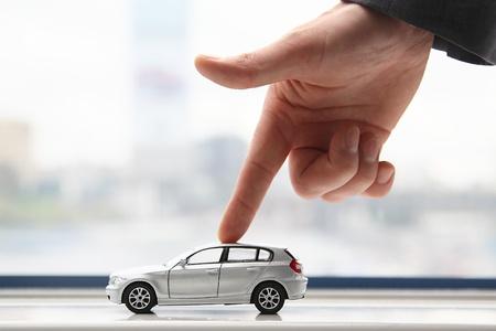 De vinger van de zakenman beweegt de speelgoedauto Stockfoto