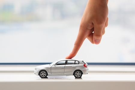 The finger of the businessman moves the toy car Stock Photo - 10988254