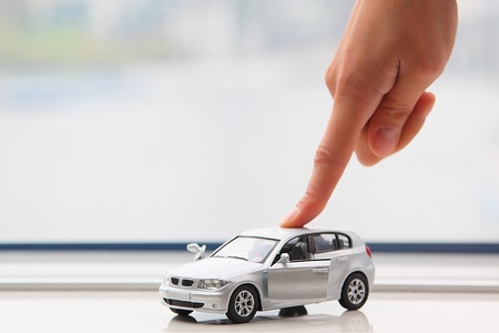 The finger of the businessman moves the toy car