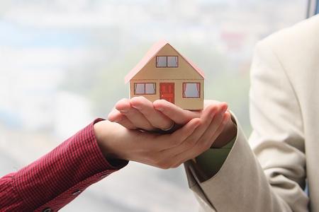 Het huis op de handpalmen naar de man en de vrouw