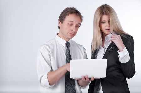 The business man and the business woman discuss the project, having control over the laptop Stock Photo - 11212270