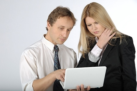 The business man and the business woman discuss the project, having control over the laptop Stock Photo - 11212478