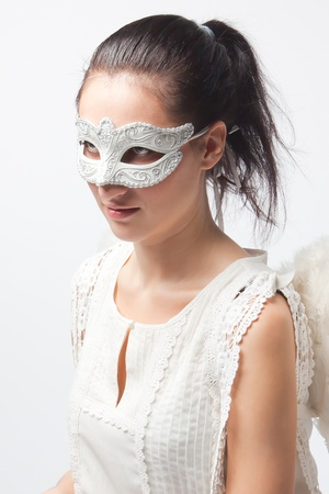 Young and beautiful girl in the mask and costume of an angel photo