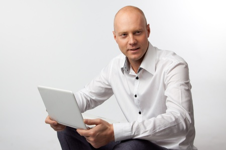Portrait of middle-aged man with a white laptop computer Stock Photo - 11424019