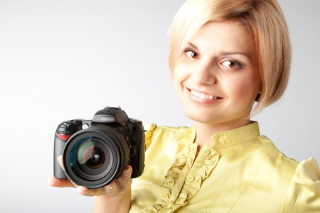 Young and beautiful girl with a professional camera in hand photo
