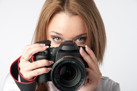 slr: Young and beautiful girl with a professional camera in hand