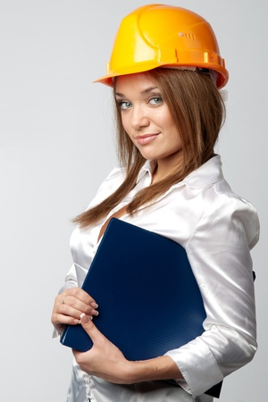 Beautiful young girl in the construction helmet photo