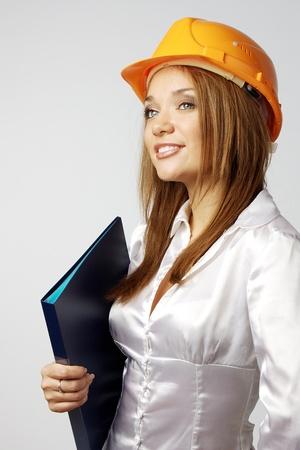 Hermosa joven en el casco de la construcción