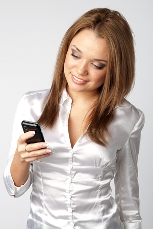 Image of young pretty people receiving SMS on your mobile phone photo