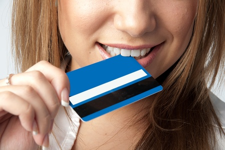 Young and beautiful girl with a credit card in the hands of blue Stock Photo - 12082839