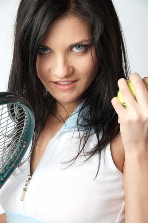 Portrait of a young and beautiful girl in tennis in the form of a racket and a ball in his hands photo