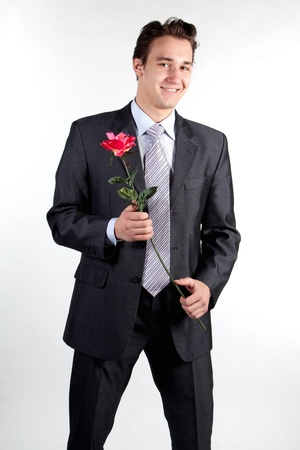 suitor: Portrait of a young successful businessman with a flower in your hand