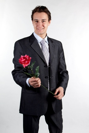 one adult only: Portrait of a young successful businessman with a flower in your hand