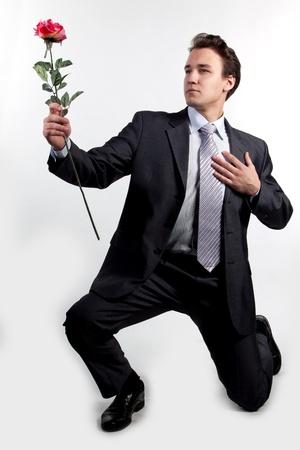 Retrato de un exitoso hombre de negocios joven con una flor en la mano