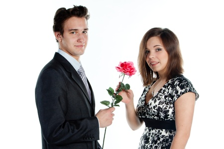 A young man gives a beautiful young woman, a flower in honor of the holiday Stock Photo - 12322479