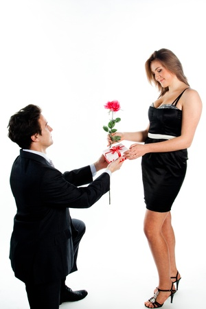 A young man gives a beautiful young woman, a flower in honor of the holiday photo
