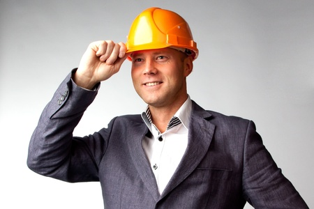 Portrait of a handsome middle-aged man in a yellow construction helmet and a business suit