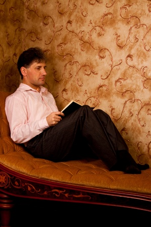Portrait of middle-aged man reading a book in the black cover at home Stock Photo - 12322102
