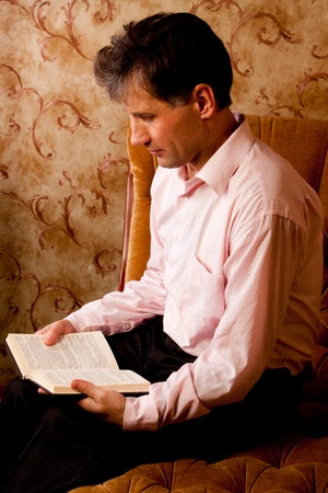 Portrait of middle-aged man reading a book in the black cover at home photo