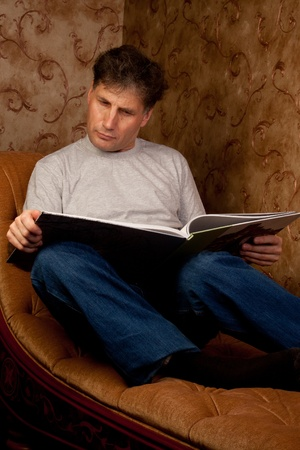 Portrait of middle-aged man reading a book in the black cover at home Stock Photo - 12322106