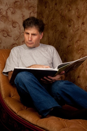 Portrait of middle-aged man reading a book in the black cover at home Stock Photo - 12322097