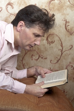Portrait of middle-aged man reading a book in the black cover at home Stock Photo - 12322101