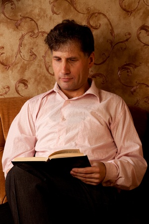 Portrait of middle-aged man reading a book in the black cover at home Stock Photo - 12322095