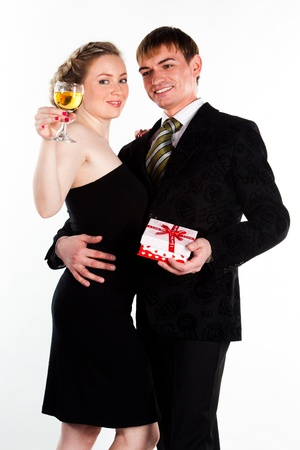 Portrait of a beautiful young couple with glasses of wine and a gift box with a red bow Stock Photo - 12321948